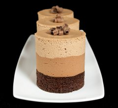 A photo of 3 Triple Chocolate Mousse Cakes displayed in a row on a white rectangular dish with a black background.