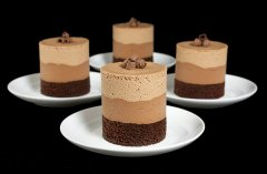 A photo of 4 Chocolate Mousse Cakes on small, white dessert dishes.