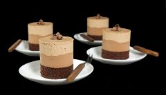 A photo of 4 Chocolate Mousse Cakes layered with Dark Chocolate Cake, Bittersweet Chocolate Mousse and Milk Chocolate Mousse displayed on small white dessert dishes with dessert forks with a black background.