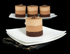A photo of 4 Triple Chocolate Mousse Cakes, one placed in front on a white dessert plate and 3 in the background on a white cake stand.