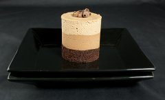 A photo of gourmet cake, Chocolate Mousse Cake with chocolate curls on a black dessert dish.
